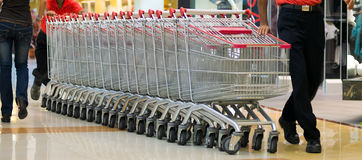 Trolleys. In a supermarket being pushed after their collection from the car parks Royalty Free Stock Photo