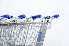Trolleys for the purchase of goods, stand in a row against the wall on a white Royalty Free Stock Photo