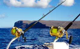 Trolling for big game. Deep sea fishing rods and reels trolling behind a fishing boat in the open ocean with a backdrop of Hawaii Stock Photos