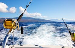 Trolling for big game. Deep sea fishing rods and reels trolling behind a fishing boat in the open ocean with a backdrop of Hawaii Stock Photography