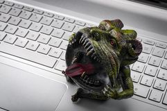 Trolling and cyber bullying concept with a troll sitting on a laptop`s keyboard. Cyberbullying in one of the major issues royalty free stock photos