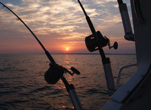 Trolling Fishing Poles. Two fishing poles silhouetted on a boat in front the sun rising on lake Michigan, set up for trolling Royalty Free Stock Image