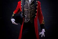 trollkarl Närbild av handen i handskar grabben i den röda camisolen och cylindern Arkivfoto
