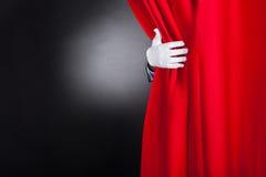 Trollkarl som öppnar den röda etappgardinen Fotografering för Bildbyråer