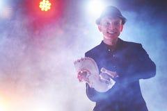 Trollkarlvisningtrick med att spela kort Magi eller skicklighet, cirkus som spelar Taskspelare i mörkt rum med dimma arkivfoton