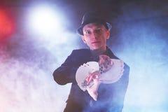 Trollkarlvisningtrick med att spela kort Magi eller skicklighet, cirkus som spelar Taskspelare i mörkt rum med dimma fotografering för bildbyråer
