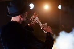 Trollkarlvisningtrick med att spela kort Magi eller skicklighet, cirkus som spelar Taskspelare i mörkt rum med dimma arkivfoto