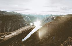 Trolltunga cliff and man traveler standing on edge in Norway. Adventure travel extreme lifestyle active vacations outdoor sunset mountains and lake royalty free stock image