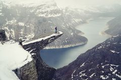 Trolltunga cliff under snow in Norway. Scenic Landscape. Man traveller standing on edge of rock and looking down. Travel