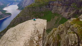 Trolltunga. Girl on the edge of a cliff. Girl on the edge of a cliff. Norway. Aerial survey. View from above.The picturesque landscape. Spectacular view stock video footage