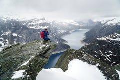 Trolltunga klippa under insnöade Norge scenisk liggande Manhandelsresanden som sitter på kanten av, vaggar och gör foto av royaltyfria foton