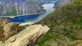 Norway. guy and girl sitting on the edge of the Trolltunga. Trolltunga. Norway. The guy and the girl sitting on the edge of the Trolltunga. aerial vie. beautiful stock video footage
