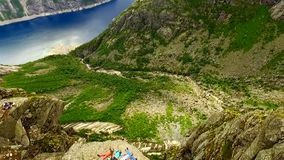 Norway. Two guys and two girls are lying on the edge of the cliff. Trolltunga. Trolltunga. Norway. Two guys and two girls are lying on the edge of the cliff on stock video