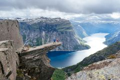 Couple of tourists on Trolltunga in Norway Stock Photos