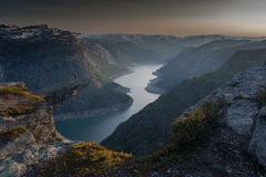 Trolltunga (Troll's tongue) - man standing on the rock above the lake Stock Photos