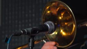 Trombón delante de un micrófono almacen de metraje de vídeo
