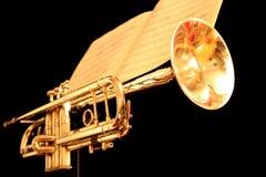 Tromba dorata con partitura su fondo nero Immagini Stock
