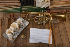 Trombeta velha coberta com a pátina em uma tabela de madeira velha Instrumento musical e livros velhos fotografia de stock