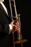 Trombone. Man in tuxedo holds a trombone, isolated on black background Royalty Free Stock Images