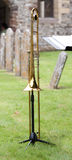 Trombone in a churchyard. Trombone on it's stand in a churchyard Royalty Free Stock Image