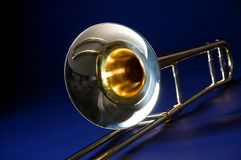 Trombone Isolated Blue Bk. A gold trombone isolated against a blue background in the horizontal or landscape view Royalty Free Stock Photography