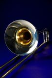 Trombone Isolated Blue Bk. A gold trombone isolated against a blue background closeup in the vertical or portrait view Stock Photo