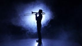 Trombone man in smoky studio playing on wind instrument, silhouette stock footage