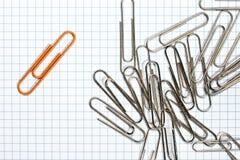 Trombone orange avec les trombones argentés Images libres de droits