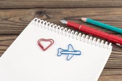 Trombone sous forme de coeur, un avion sur un bloc-notes, stylo, crayon sur un fond en bois Image libre de droits