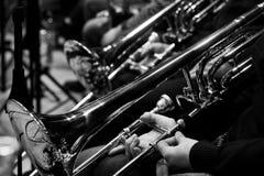Trombones dans les mains des musiciens Photographie stock libre de droits