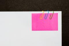 Trombones et post-it colorés sur le fond blanc d'isolement photographie stock libre de droits