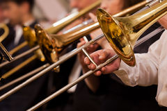 Trombones in the hands of musicians Royalty Free Stock Photos
