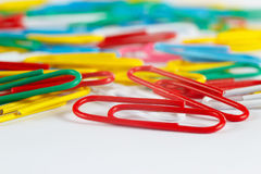 Trombones multicolores de bureau sur le plan rapproché de bureau blanc Photographie stock
