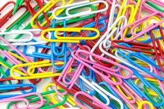 Trombones multicolores en vrac le mensonge sur un fond blanc Fin vers le haut photographie stock libre de droits