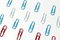 Trombones multicolores sur un fond blanc, concept de bureau photographie stock