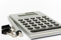 Une calculatrice et un stylo sur un fond blanc Photographie stock libre de droits
