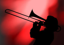 Trombonist silhouette. A trombone musician plays his trombone against a colorful backgound Royalty Free Stock Photos