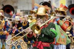 Trombonspelaren i färgrik marschmusikband på karnevalet ståtar, St Royaltyfri Foto