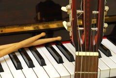 Trommelsteuerknüppel, Gitarre und Klaviertastatur Stockfotografie
