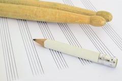 Trommelstokken, een potlood en een muziekblad op een bureau in een klaslokaal lege exemplaarruimte Royalty-vrije Stock Foto