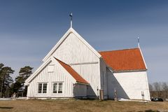 Tromoy church at Hove, Tromoy in Arendal, Norway. White church, blue sky, sunny day. Pebble shore at Hove, Tromoy in Arendal, Norway. Raet National Park. Long Royalty Free Stock Image