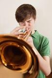 Trompeta adolescente del oro que juega Imagen de archivo libre de regalías