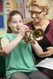Trompeta del juego de Helping Pupil To del profesor en la lección de música foto de archivo