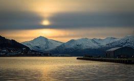 Tromso berg fördunklar det ljus- och solTroms länet, nordliga Norge Arkivfoto