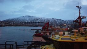 Tromso Bridge across Tromsoysundet strait and Tromso harbour. Port and harbour with famous Tromso Bridge across Tromsoysundet strait in the background, Northern stock video footage