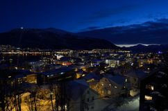 Tromso city at winter snowy night with light,traffic,fjord and motion with mainland Royalty Free Stock Photos