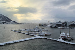 Tromso, Norway. Docks at Tromso, Norway, covered by snow and with sunlight shining, sky with clouds stock photography