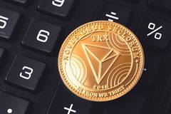 Tron cryptocurrency coin. Tron cryptocurrency on the black calculator stock images
