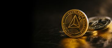 Tron cryptocurrency. Closeup of golden tron coin TRX cryptocurrency over black and gold background. Virtual money altcoin and blockchain concept stock photography