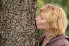 Tronco de árbol de la mujer que se besa madura Foto de archivo libre de regalías